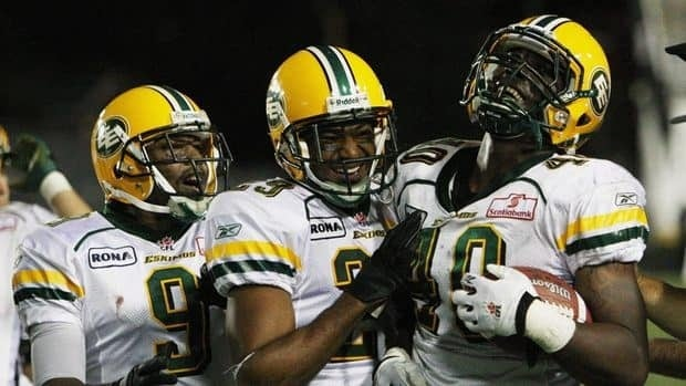 Edmonton Eskimos' Rod Davis, right, celebrates with teammates after recovering a fumble against the Hamilton Tiger-Cats.