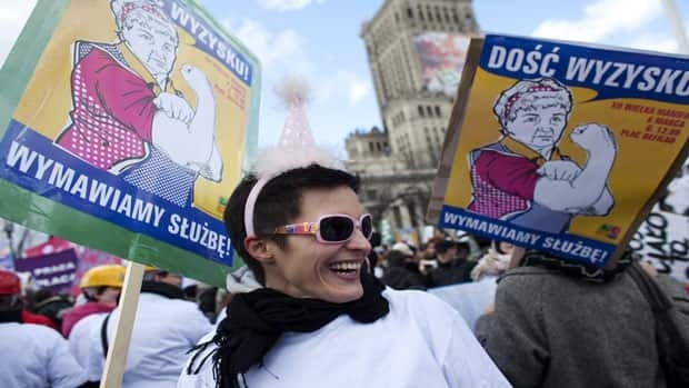 A woman holds a sign reading 'Enough exploitation, we refuse service' during a demonstation in Warsaw on March 6, in anticipation of International Women's Day.