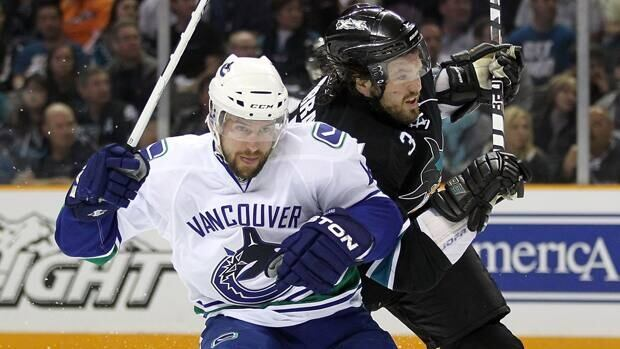 Keith Ballard, left, jostles with Sharks defenceman Douglas Murray in Sunday's 4-2 Canucks triumph in Game 4 at HP Pavilion.