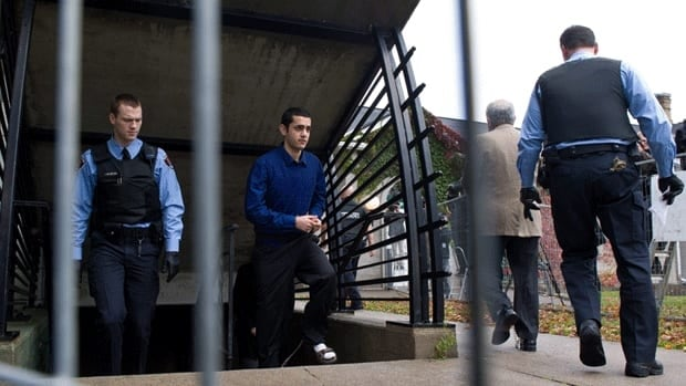 Hamed Mohammed Shafia is escorted by police officers to the courtroom on the first day of trial in October.