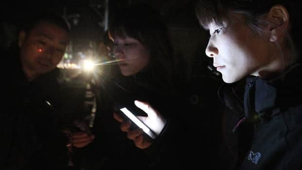 Hotel guests check their mobile phones for earthquake news after they evacuated the building following an aftershock, in Ichinoseki, Iwate Prefecture, Japan, Friday.