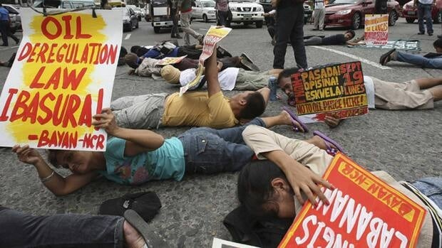 Protesters lie prone on the pavement to do a planking, blocking briefly the traffic at a busy roundabout in Manila, Philippines, Monday.