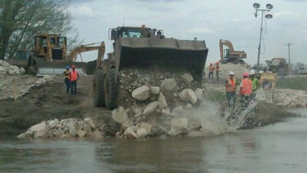 Crews begin work to close the controlled release at the Hoop and Holler Bend on the Assiniboine River on Friday.