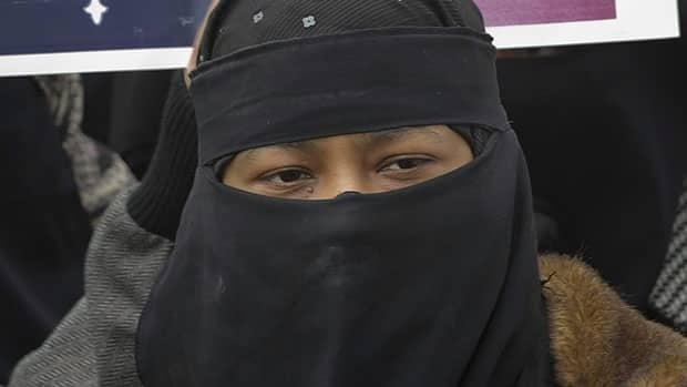 A woman wearing a niqab demonstrates against Quebec's Bill 94 requiring people to uncover their faces to receive government services, in April 2010. Federal Immigration Minister Jason Kenney said Monday a similar rule is in place to take an oath of citizenship.
