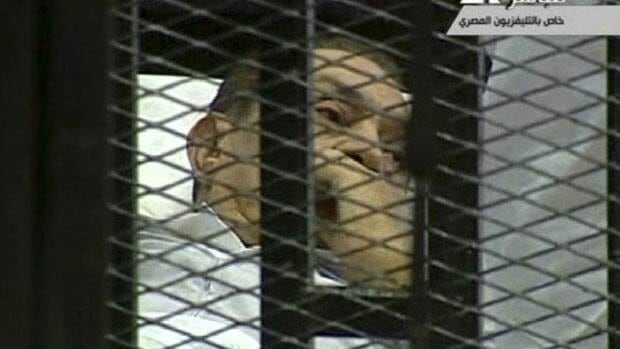 Hosni Mubarak, in an image taken from Egyptian State Television, is on a hospital bed inside a cage of mesh and iron bars in a Cairo courtroom on Wednesday for the start of his trial on charges of corruption and ordering the killing of protesters during the uprising that ousted him.