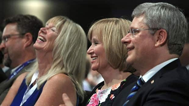 Prime Minister Stephen Harper, right, shares a laugh with his wife Laureen Harper, second from right, and Valerie Day, as her husband, former MP Stockwell Day, addresses the Conservative convention on Thursday.
