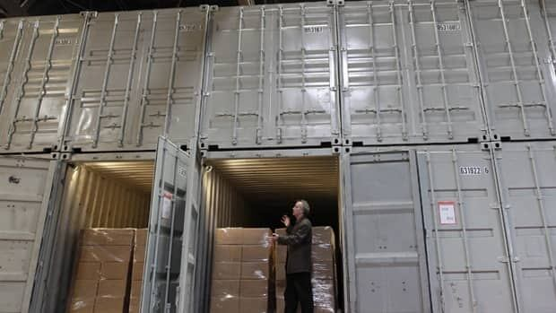 Internet pioneer Brewster Kahle wants to store a copy of every book ever published. He's shown here with the converted shipping containers used to store the books at the Internet Archive's warehouse in Richmond, Calif.