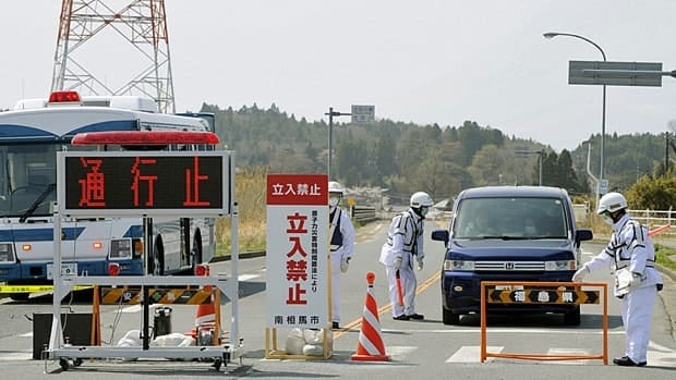 Residents speak to police officers as they leave the evacuation zone around the crippled Fukushima Daiichi nuclear plant on Thursday.