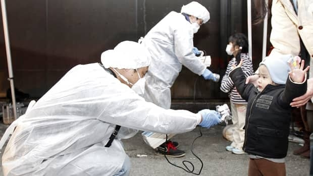 Officials in protective gear check for signs of radiation on children from the evacuation area near the Fukushima Daiichi nuclear plant in northest Japan on March 13.