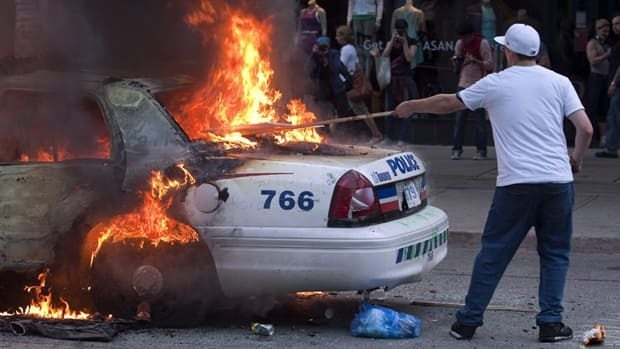A man stands near a flaming police car during an anti-G20 demonstration in Toronto on June 26, 2010. More than 1,100 people were rounded up that weekend.