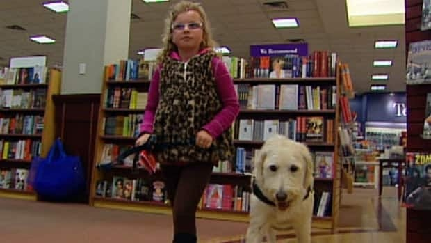Emily Ainsworth with service dog Levi shop in a west Edmonton book store Monday. Emily and Levi were asked to leave a nearby clothing store Sunday.