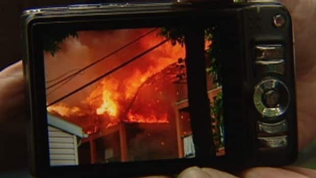 Normand Hachey, a tenant of an apartment building damaged by fire Tuesday, shows off his photos of the fire.