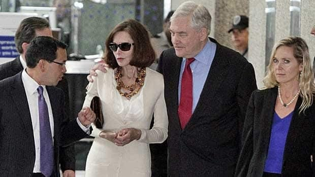 Conrad Black and his wife Barbara Amiel Black listen to attorney Miguel Estrada as they leave federal court in Chicago June 24, 2011, after his sentencing. Black surrendered to prison in Miami Tuesday.