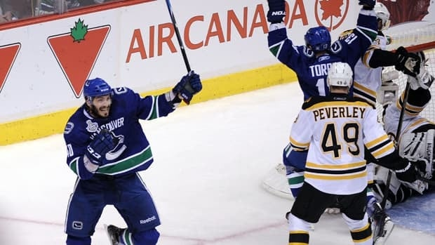 Vancouver centre Maxim Lapierre, left, celebrates his third-period goal against the Boston Bruins Friday night at Rogers Arena.