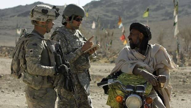 A US Army sergeant, left, and an Afghan interpreter, centre, speak to an Afghan man during a foot patrol in Kandahar province, Nov. 24, 2010. Strict requirements have limited the number of successful applications of Afghan interpreters who served with the Canadian Forces to come to Canada as refugees.