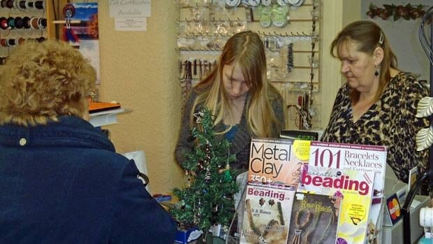 Susan Frost, right, owner of Jangles, a beading store in Thunder Bay, asks her customers to pay with cash instead of using their premium credit cards.
