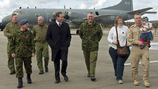 Defence Minister Peter MacKay, in black, and Col. Jim Irvine, to Mackay's left, greet air crew  in Greenwood, N.S., as they return from Operation Mobile, Canada's military mission in Libya on Nov. 5. Irvine is the base commander at Canadian Forces Base Greenwood.