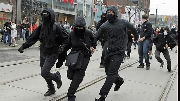 Masked protesters run through the streets during demonstrations against the June 2010 G20 summit in downtown Toronto.