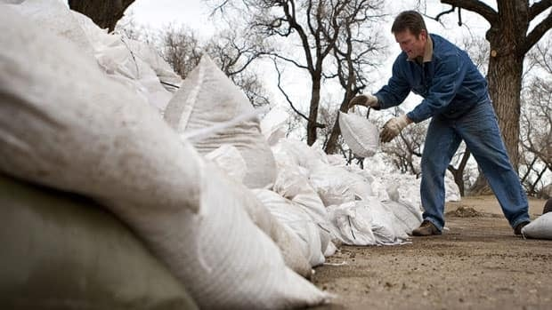 David Stickel, an employee of Saamis Funeral Home in Medicine Hat, Alta., sandbags the perimeter of the business earlier this week.