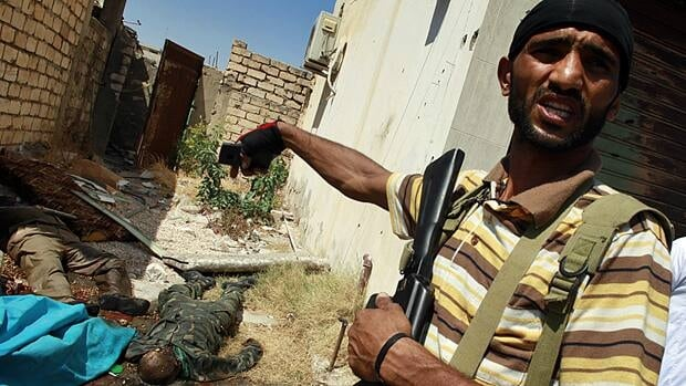 A Libyan rebel fighter points to the bodies of pro-Gaddafi soldiers killed after rebels seized control of the centre of the strategic coastal city of Zawiyah on Saturday.