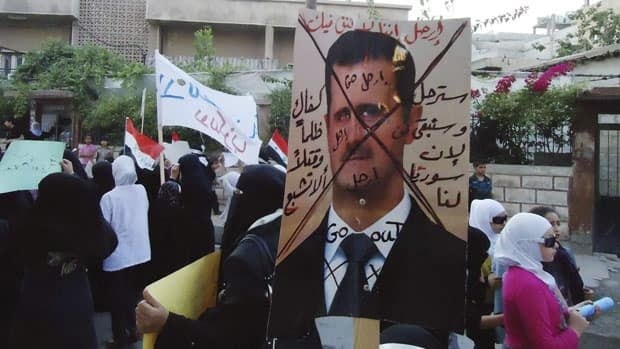 Syrian anti-regime protesters carry a picture of President Bashar al-Assad with Arabic writing that reads 'Leave. We don't trust you. You will leave and we will stay because Syria is ours. Enough of injustice and killing,' in this citizen journalism image taken with a mobile phone and provided by Shaam News Network.