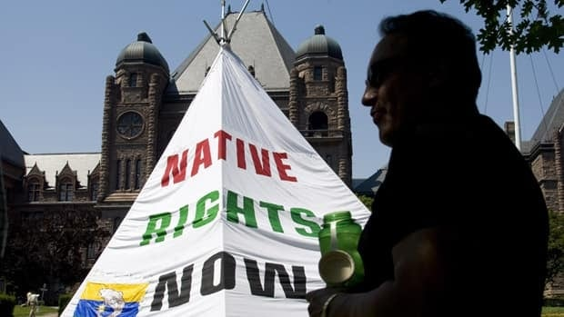 John Cutfeet is silhouetted outside the provincial legislature in Toronto, on June 25, 2007, after a teepee was erected by members of the Grassy Narrows and Kitchenuhmaykoosib Inninuwug First Nations to draw attention to logging and mineral extraction on their traditional lands.