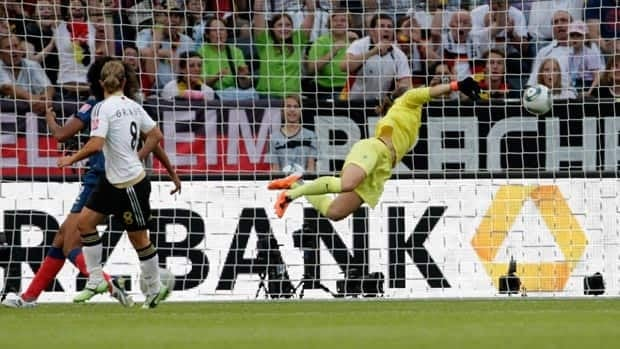 Germany's Inka Grings, left, finishes off a beautiful header over French goalkeeper Berangere Sapowicz Tuesday in Moenchengladbach. The victory secured Group A for the Germans.