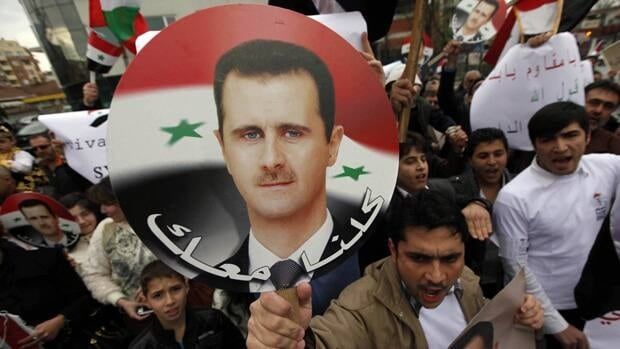 Syrian President Bashar Assad, shown here on a supporter's poster, will lose any assets he has under U.S. jurisdiction, thanks to new sanctions against him and several close supporters.