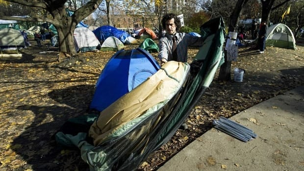 An Occupy Toronto protester takes down his tent after being served with an eviction notice. The forced removal of protesters from public spaces in other North American cities have cast the movement's future into doubt.