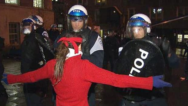 Montreal police confront a protester in front of the McGill University's James Administration Building Thursday night.