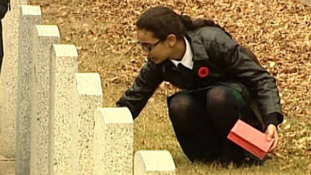 Grade 8 student Manroop Randhawa lays poppies Thursday on individual graves of fallen soldiers at Beechmount Cemetery in Edmonton.