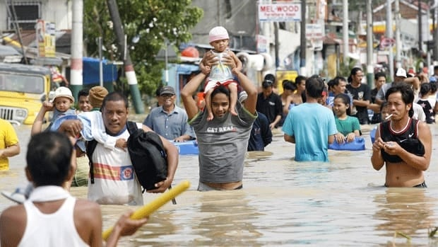 Villagers north of the Philippine capital, Manila, wade through floodwaters caused by Typhoon Nalgae on Oct. 2, 2011. Typhoons, cyclones and other severe weather events are becoming more frequent and are taking a greater toll on the world's population, says a report by the Intergovernmental Panel on Climate Change.
