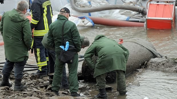 Firefighters and police look at a massive Second World War bomb in the Rhine near Koblenz, Germany on Dec. 3, 2011. The bomb was discovered along with another smaller one after water levels fell significantly.