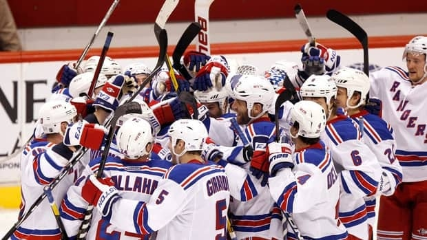 New York Rangers players swarm teammate Brad Richards, centre, after it was determined he scored the game-winning goal in the final seconds of the third period against the Phoenix Coyotes on Saturday in Glendale, Ariz. The Rangers won 3-2.