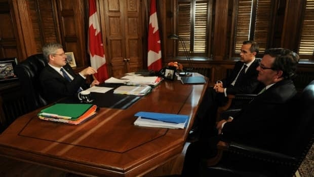 Prime Minister Stephen Harper speaks with Finance Minister Jim Flaherty and Bank of Canada Governor Mark Carney during a meeting in his office on Parliament Hill on Tuesday.