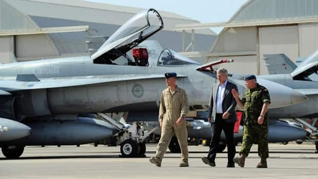 Prime Minister Stephen Harper, middle, gets a tour of Canada's CF-18s by Lt.-Col. Daniel McLeod, left, and Gen. Charles Bouchard prior to delivering a speech at Camp Fortin on the Trapani-Birgi Air Force Base in Trapani, Italy. After seven months in the country, the Canadian Forces will be back in Canada Friday.