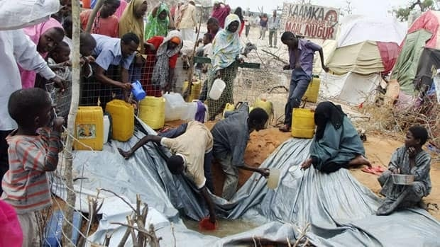 Refugees from southern Somalia fill receptacles with rain water, at a refugee camp in Mogadishu, Somalia, Sept. 5, 2011. About 750,000 more people may die from famine in the next four months if there is no adequate response, the UN Food Security and Nutrition Analysis Unit for Somalia said, an increase of 66 percent from July. Canadians have so far contributed $35.8 million to aid agencies doing famine relief work.