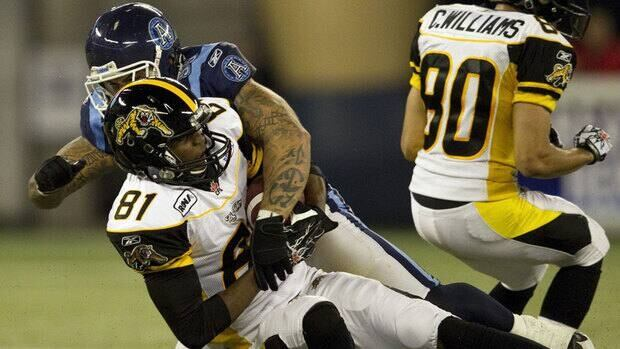 Toronto Argonauts defensive end Ricky Foley (95) tackles Hamilton Tiger-Cats wide receiver Aaron Kelly (81) during the first half Thursday in Toronto.