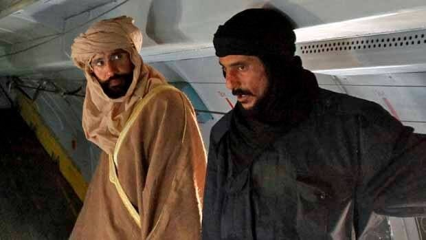 Saif al-Islam Gaddafi, left, stands in a plane in Zintan on Saturday. He told Reuters he was feeling fine after being captured by some of the fighters who overthrew his father.