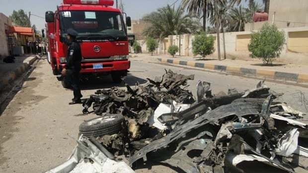 Iraqi rescue teams arrive at the scene of two car bombs that ripped through a group of police officers outside the local governor's home in the central Iraqi city of Diwaniyah.