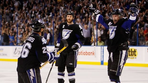 Martin St. Louis (26) celebrates his second period goal with Steven Stamkos (91) and Eric Brewer (2) of the Tampa Bay Lightning in Game 6 of the Eastern Conference Finals against the Boston Bruins on Wednesday in Tampa, Florida.