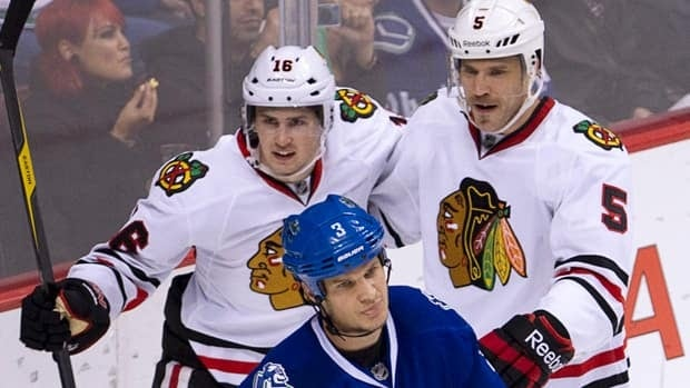 Chicago Blackhawks centre Marcus Kruger (16) and Steve Montador (5) celebrate teammate Andrew Brunette's goal during  the second period as Vancouver Canucks defenseman Kevin Bieksa (3) looks on in Vancouver on Wednesday.