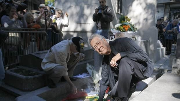The Doors guitarist Robby Krieger, left, and keyboardist Ray Manzarek light candles at the grave of Jim Morrison in Paris on Monday.