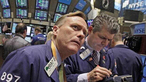 Traders Paul Lawless, left, and John Panin work on the floor of the New York Stock Exchange on Monday. U.S. markets also fell Wednesday, weighed down by unexpectedly weak American jobs data.