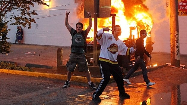 People pose in front of a burning vehicle during a riot that broke out in downtown Vancouver after the Vancouver Canucks lost the Stanley Cup final to the Boston Bruins.