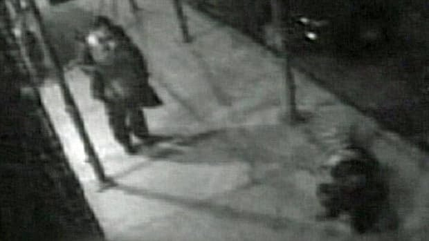 In this frame grab from an April 18, 2010, surveillance video obtained by ABC, a pedestrian approaches Hugo Tale-Yax, lower right, lying on the ground after he was stabbed following his effort to help a woman being attacked in the Queens borough of New York.
