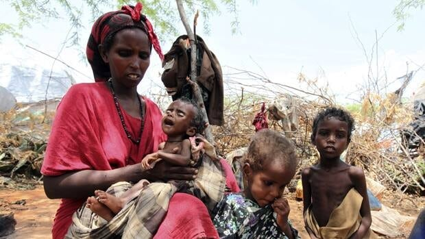 A malnourished woman carries her child outside their makeshift shelter at a temporary camp in Somalia's capital, Mogadishu, in August. Camps in Mogadishu remain in the famine zone, despite downgrades elsewhere.