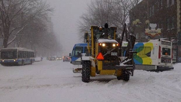 A Montreal city bus got stuck in the snow as a plow drives by at the corner of Sherbrooke Street and Oxford Street.