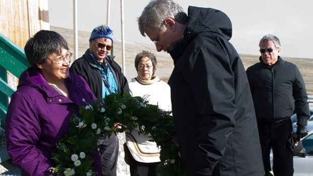 Prime Minister Stephen Harper presents a wreath to Resolute Mayor Tabatha Mullin in memory of the 12 lives lost in the crash of a First Air plane on Saturday. Harper visited the Nunavut hamlet as part of four-day tour of Arctic communities.