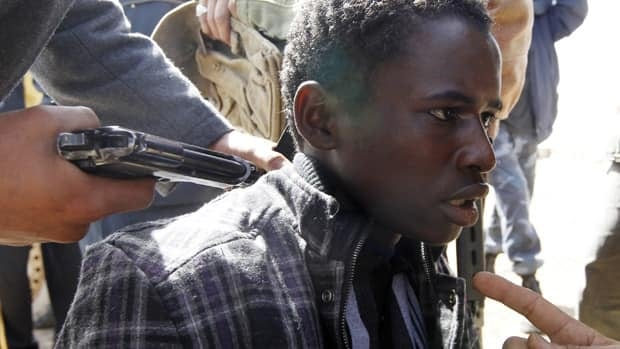 Anti-Gadhafi fighters hold a young man at gunpoint in March. They accused him of being a Gadhafi loyalist. Amnesty International is calling on the transitional government to do more to promote human rights, saying it found evidence of abuse on both sides of the Libyan conflict.
